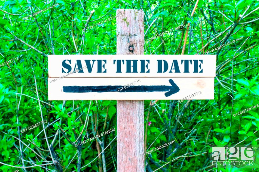 Stock Photo: SAVE THE DATE written on Directional wooden sign with arrow pointing to the right against green leaves background. Concept image with available copy space.