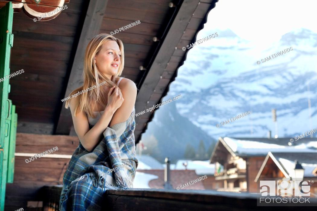 Stock Photo: Smiling woman wrapped in a blanket and looking at view on cabin porch.