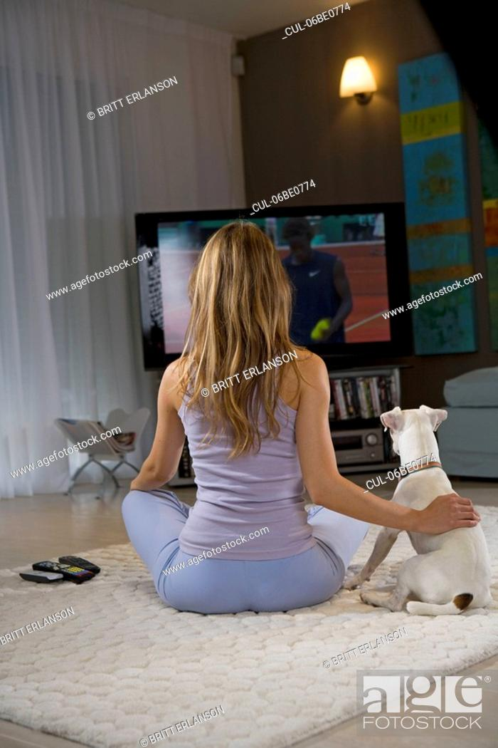 Stock Photo: Woman and dog watching tv.