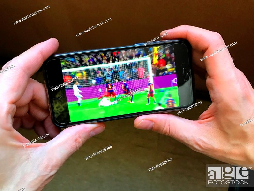 Stock Photo: Man's hand holding a smartphone, watching a football match.