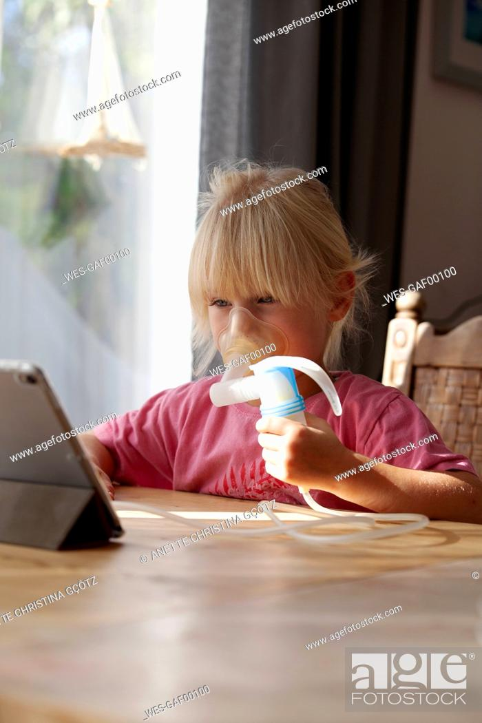 Stock Photo: Portrait of blond little girl using asthma inhaler while looking at digital tablet.