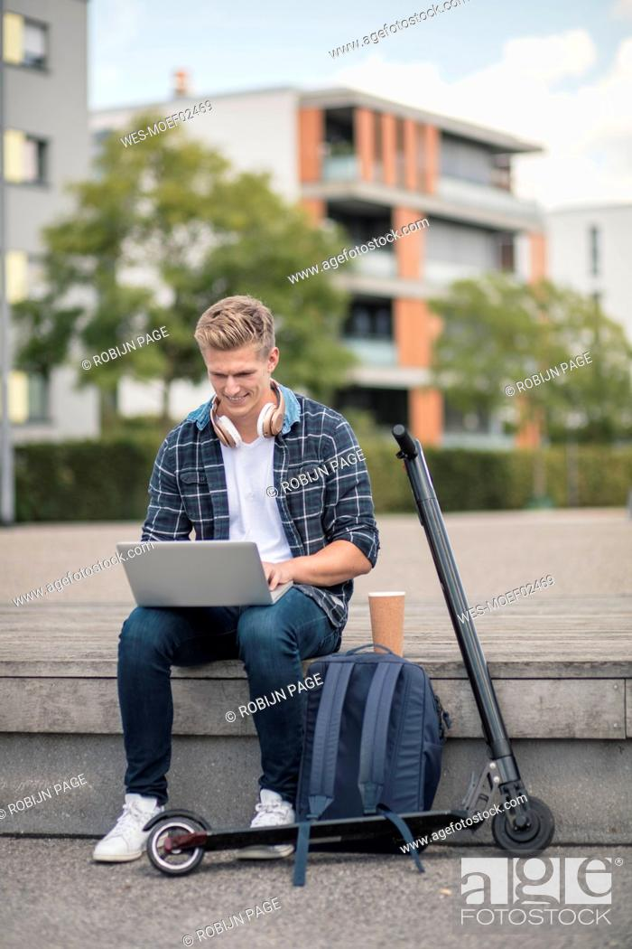 Stock Photo: Young businessman with e-scooter using laptop in the city.