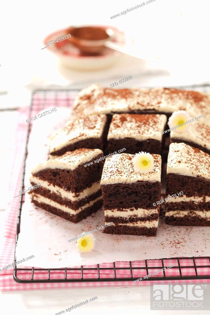 Stock Photo: Tiramisu torte, sliced into pieces.