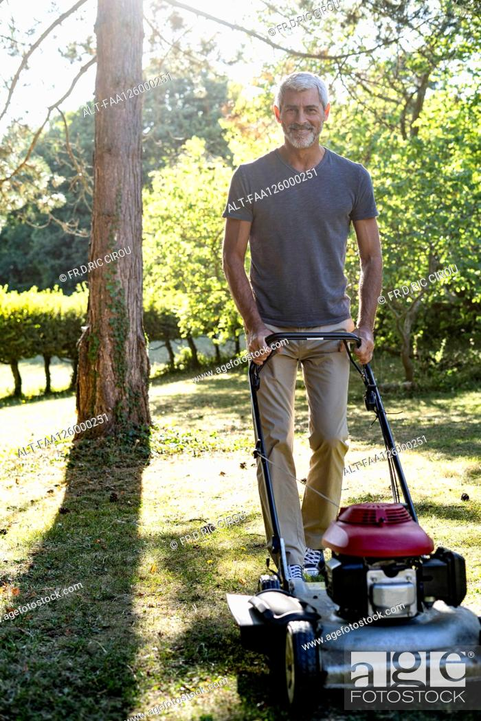 Photo de stock: Portrait of smiling mature man mowing grass with mower.