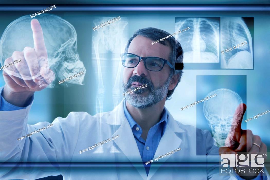 Stock Photo: Hispanic doctor examining x-rays on virtual screen.