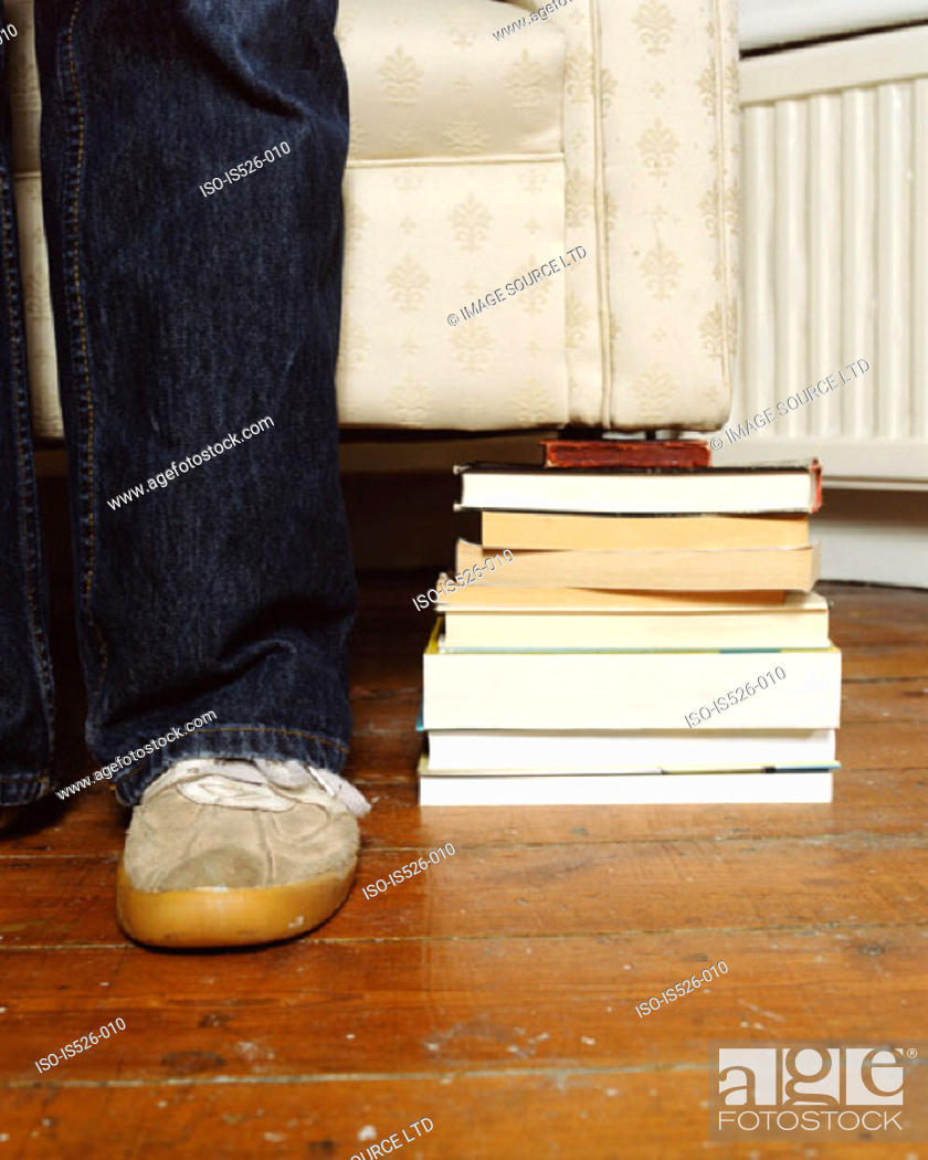Stock Photo: A pile of books holding a sofa.