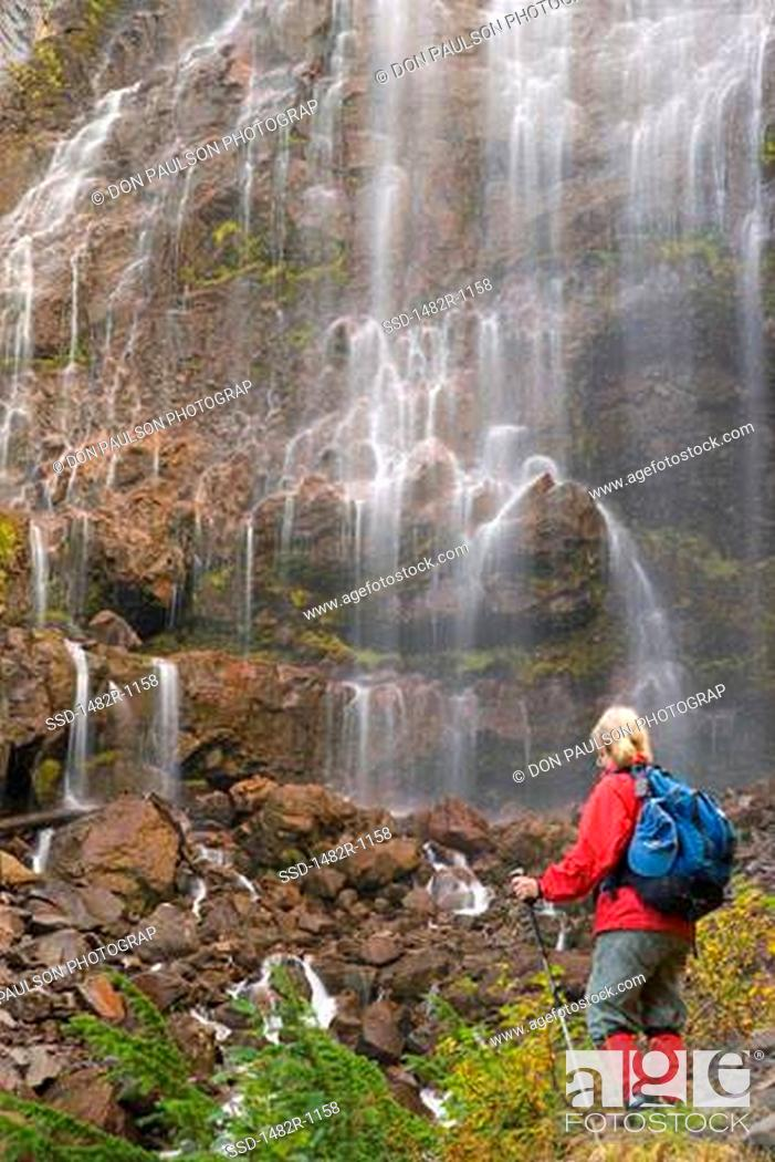 Stock Photo: Rear view of a woman standing near a waterfall, Spray Falls, Mount Rainier National Park, Washington, USA.