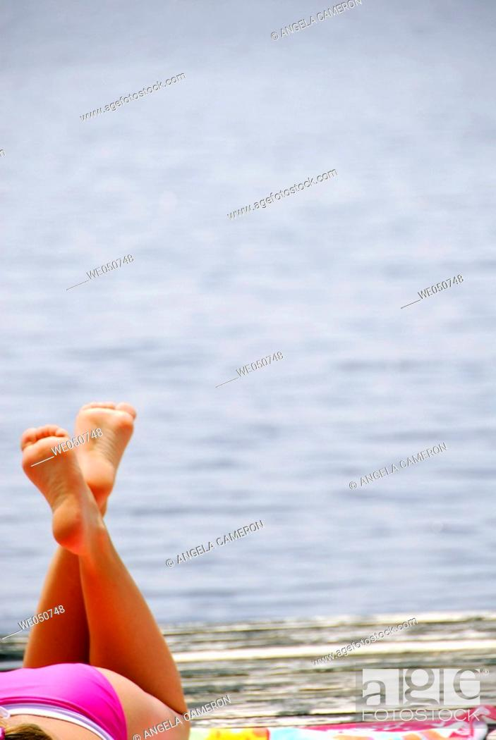 Stock Photo: 18 yr old girl laying on dock.