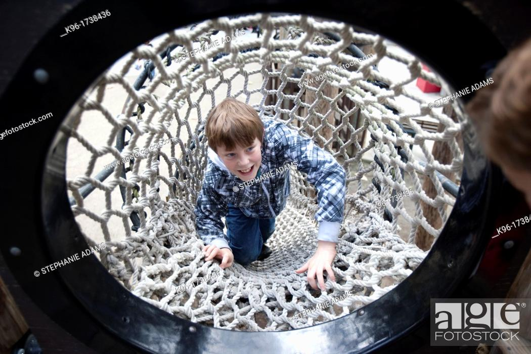 Stock Photo: boy laughing while climbing a rope tunnel.