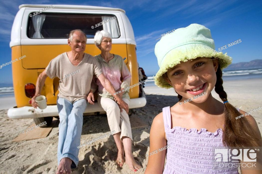 Stock Photo: Girl 7-9 on beach by grandparents sitting on back of camper van, smiling, portrait.