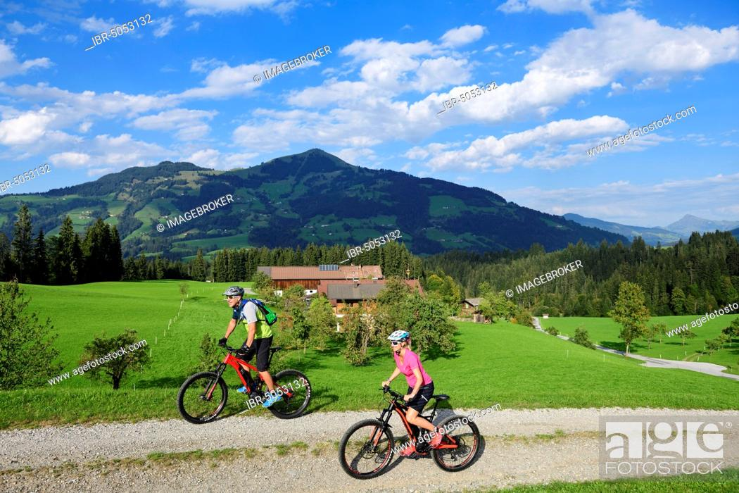 Imagen: Two cyclists with electric mountain bikes on the Glantersberg with view of the Hohe Salve, Kitzbühel Alps, Tyrol, Austria, Europe.
