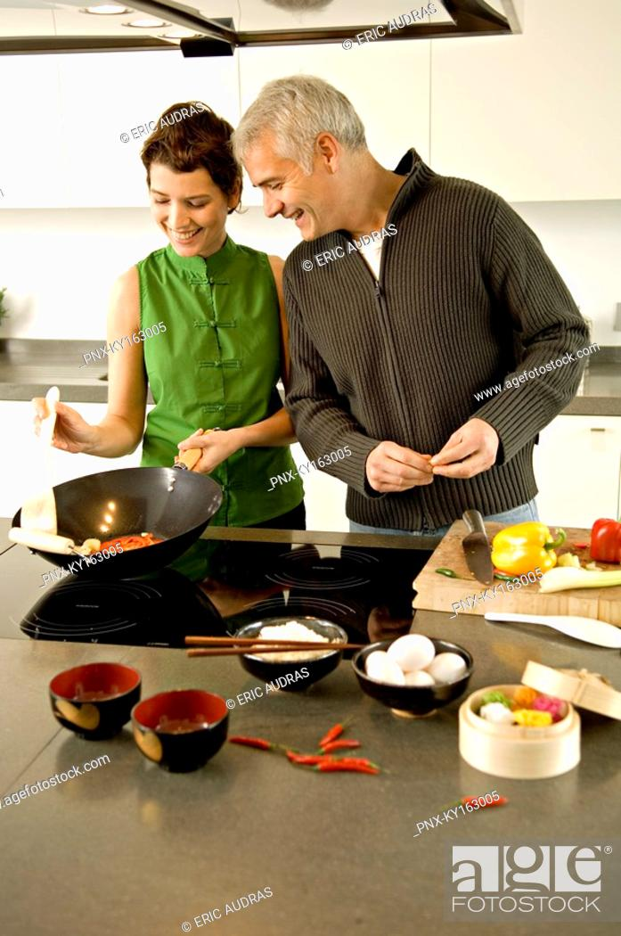 Stock Photo: Mature man and a mid adult woman preparing food in the kitchen.