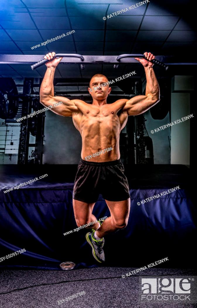 Stock Photo: Young sportsman pulls up on a horizontal bar in a gym.