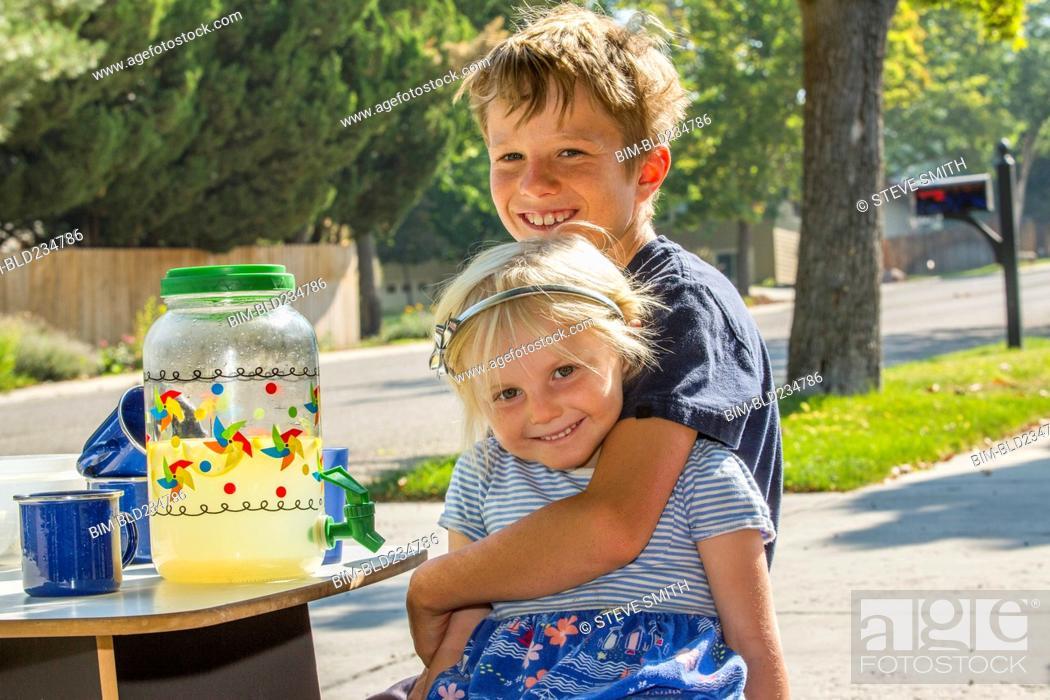 Stock Photo: Smiling Caucasian boy hugging girl and selling lemonade.