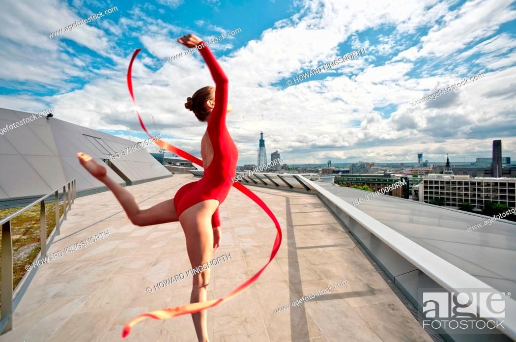 Imagen: Dancer with ribbon on urban rooftop.