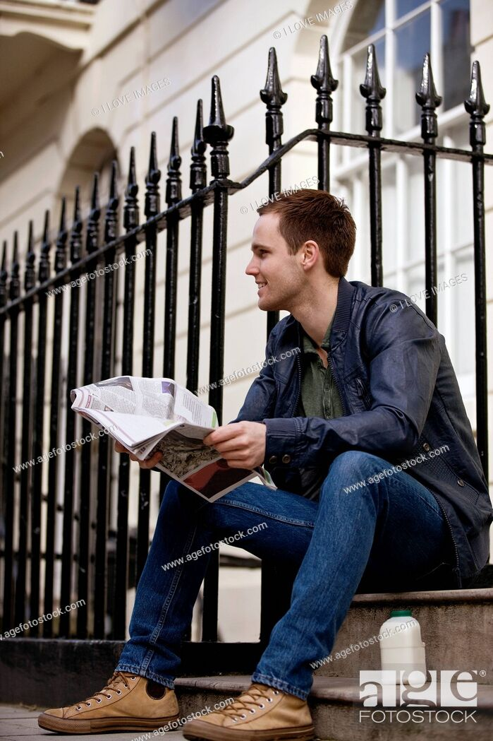 Stock Photo: A young man sitting on a step, reading a newspaper.