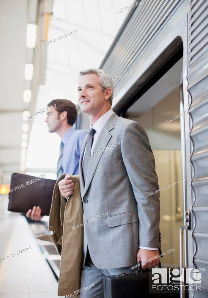 Stock Photo: Businessmen exiting train in train station.