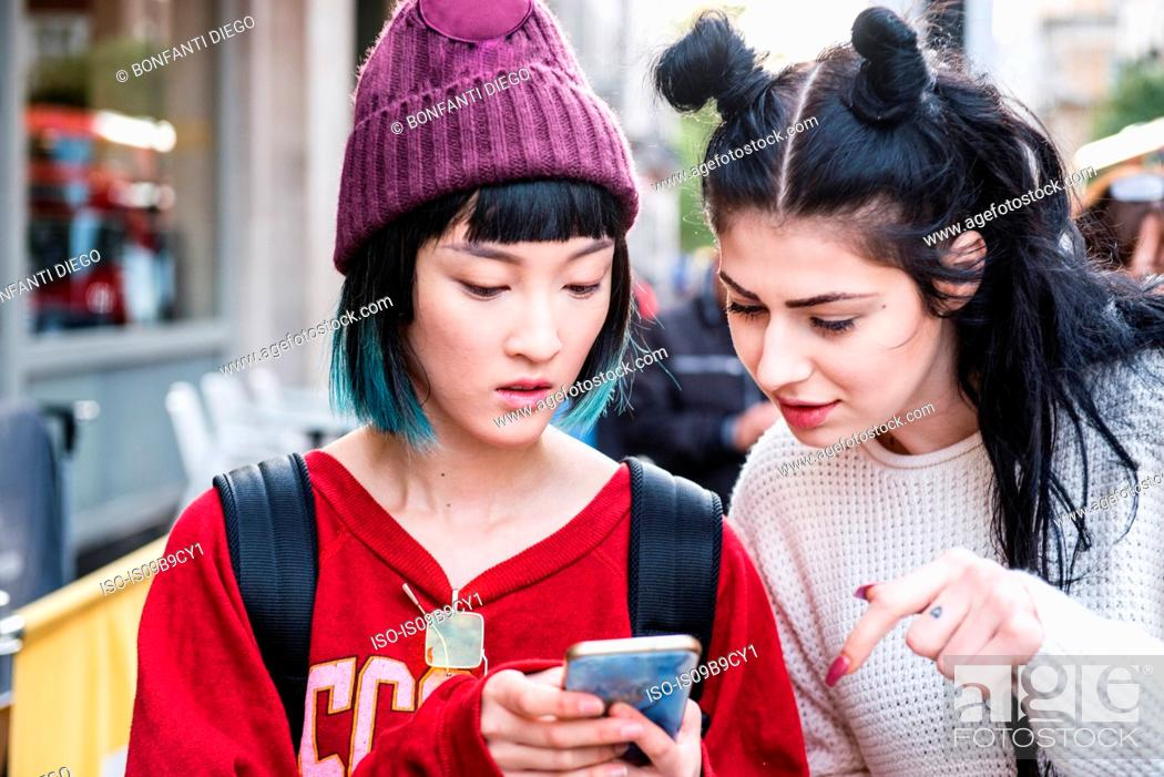 Stock Photo: Two young stylish women looking at smartphone on city street.