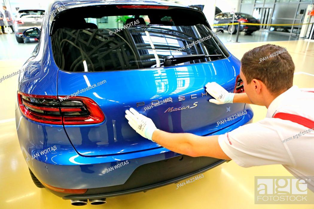 A Porsche employee checks the lettering on a new Porsche