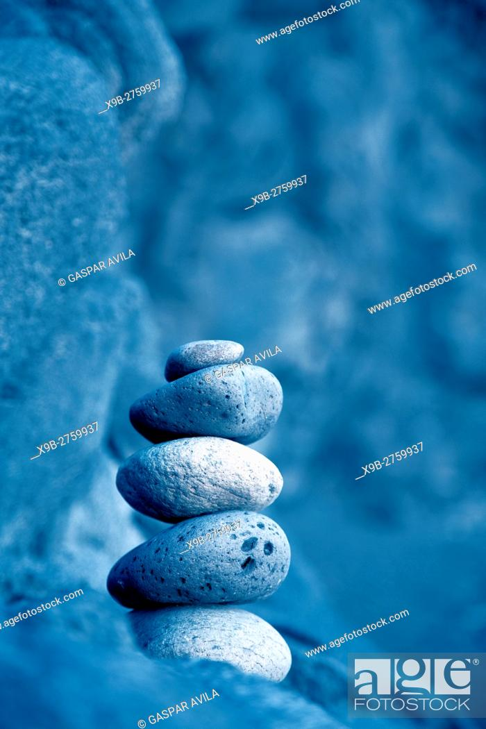 Stock Photo: Stacked pebbles outdoors. Digital blue coloring filter was applied.