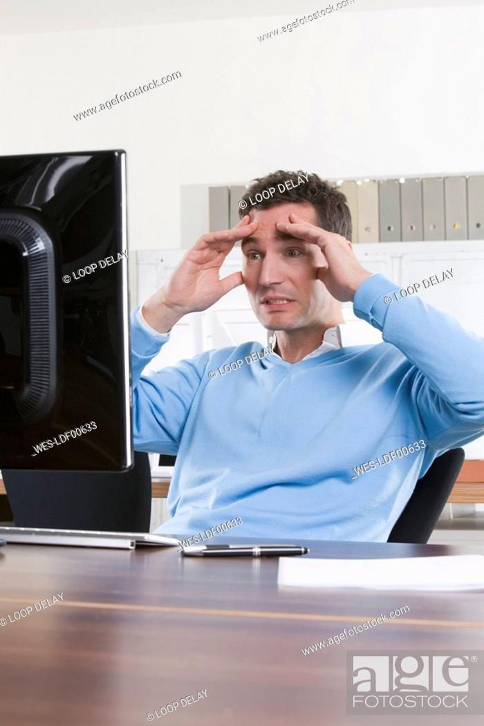 Stock Photo: Germany, Munich, business man in office, hands on head, portrait.