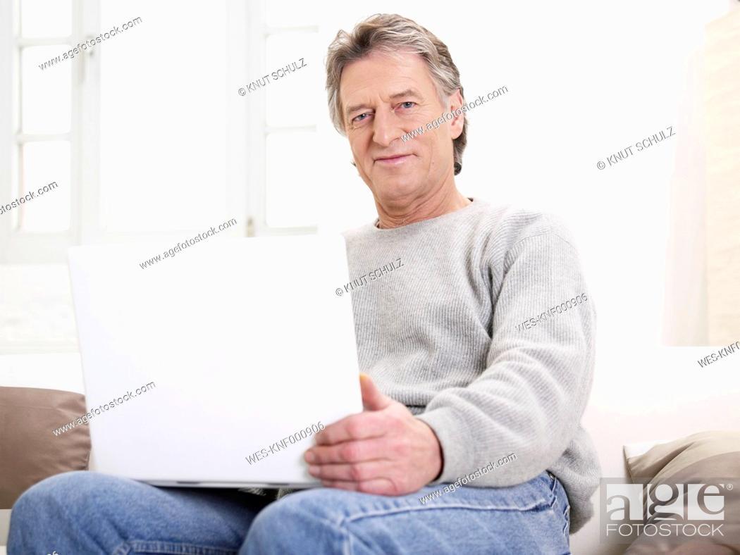 Stock Photo: Germany, Hamburg, Senior man using laptop, portrait.
