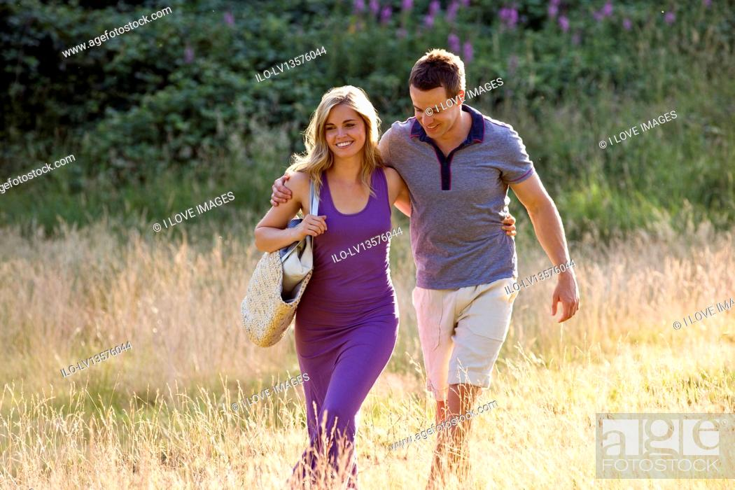 Stock Photo: A young couple walking through a field arm in arm.