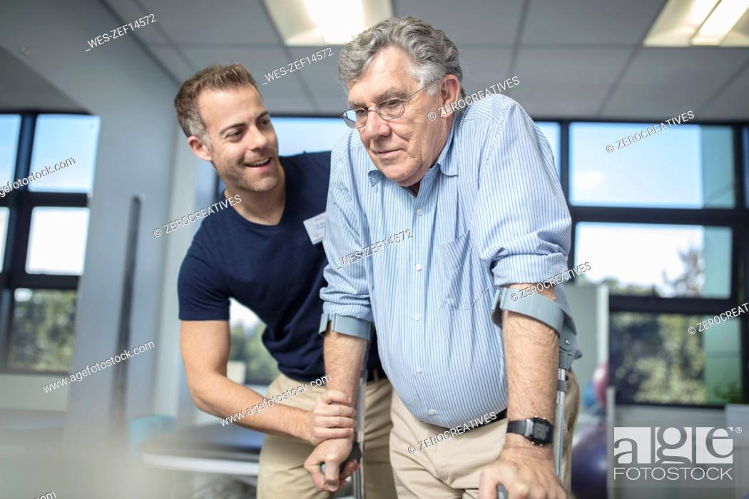 Stock Photo: Physio helping senior patient with crutches.