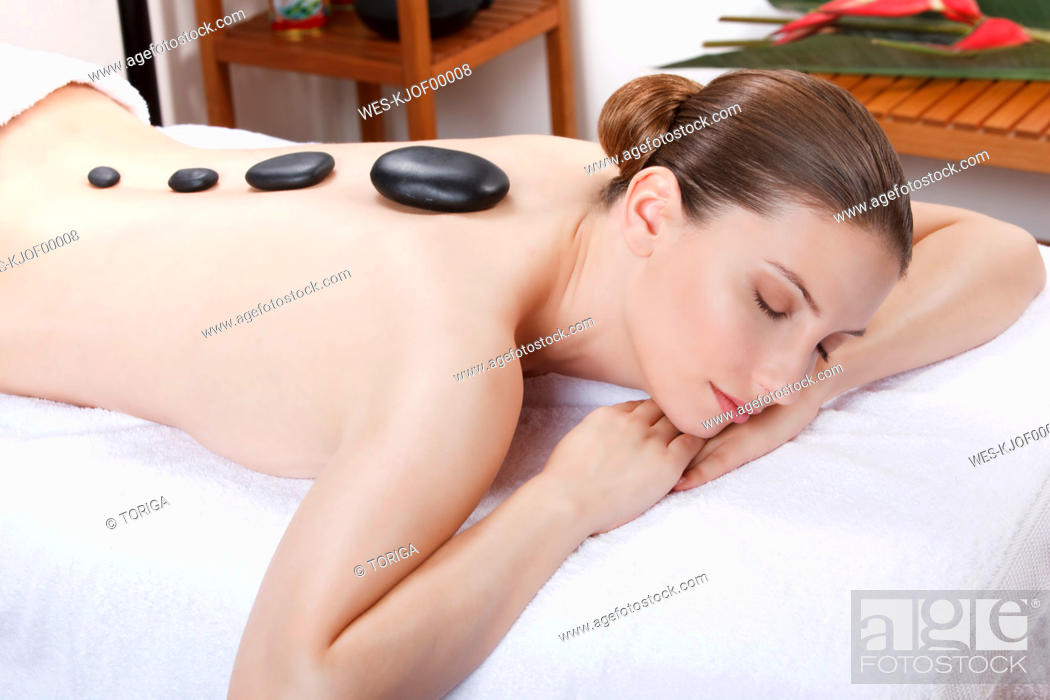 Stock Photo: Woman having a hot stone treatment, eyes closed.