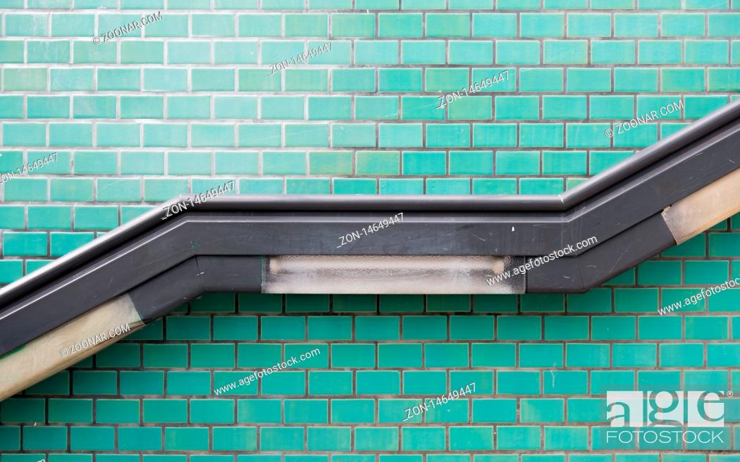 Stock Photo: The handrail up the stairs and the turquoise tiled wall.