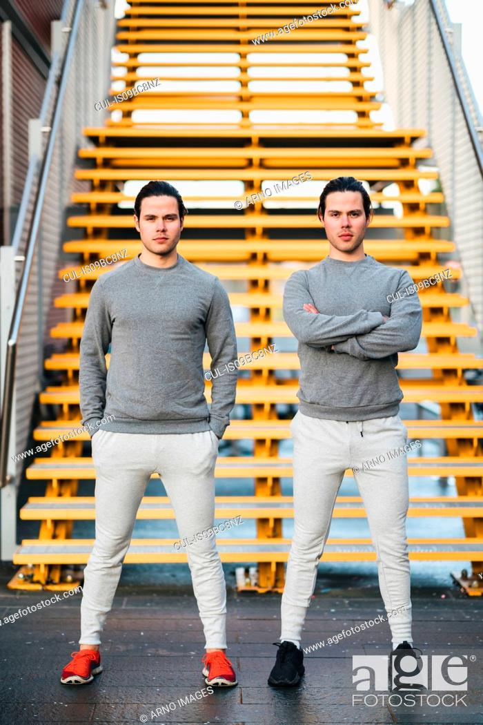 Photo de stock: Young adult male twins training together, stairway portrait.