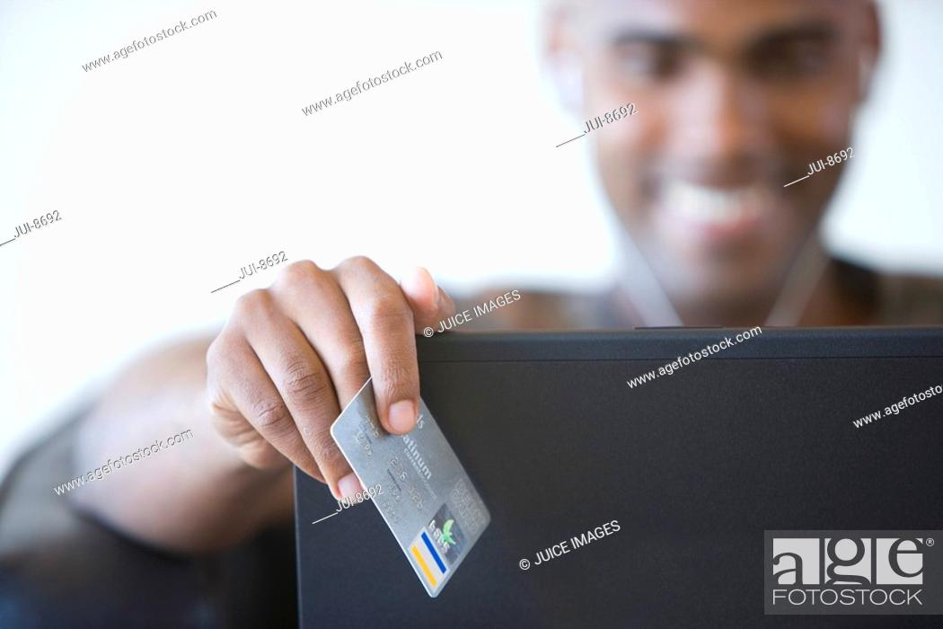 Stock Photo: Young man credit card by laptop, smiling, portrait focus on credit card.