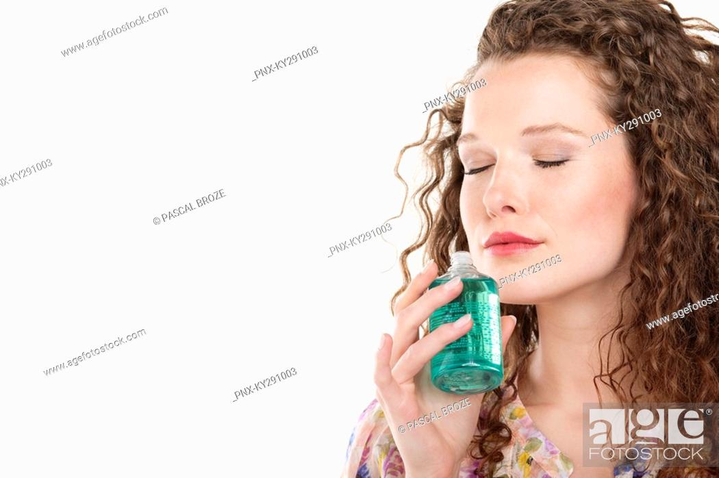 Stock Photo: Woman smelling aromatherapy oil.