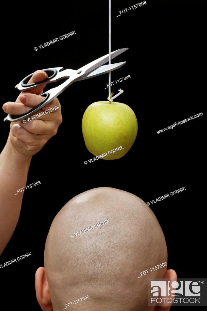 Stock Photo: A woman cutting an apple on a string above the head of a man.