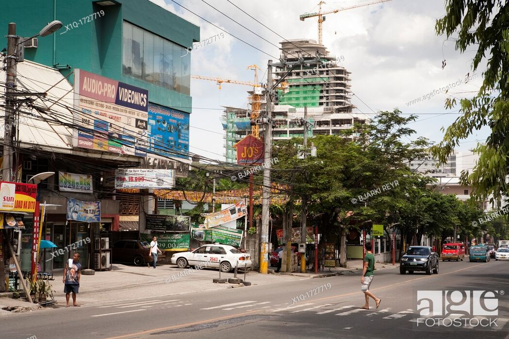 Photo de stock: Man crossing the road, the highrise building under construction in the background is part of Asiatown IT Park  Cebu City, Cebu, Visayas, Philippines.