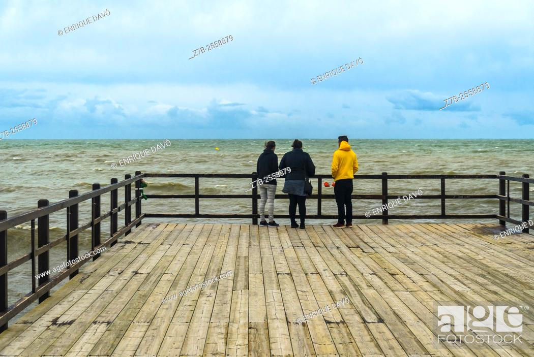 Stock Photo: Three people in La Gola beach, Santa Pola, Alicante province, Spain.