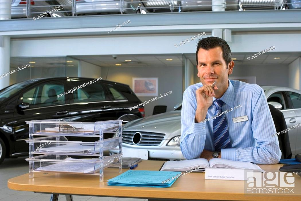 Stock Photo: Car salesman sitting at desk in car showroom, smiling, portrait.