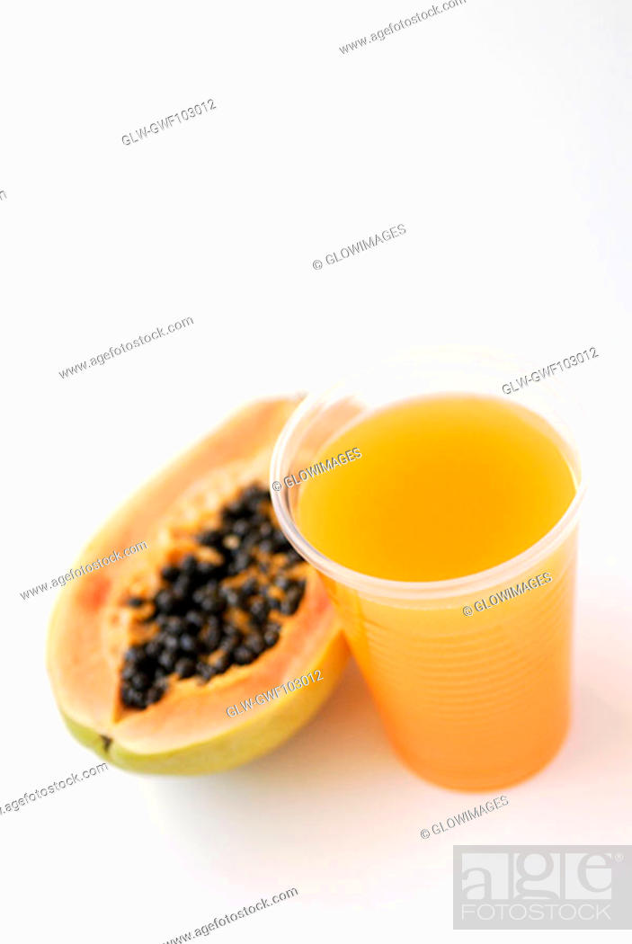 Stock Photo: High angle view of a glass of juice with a papaya.