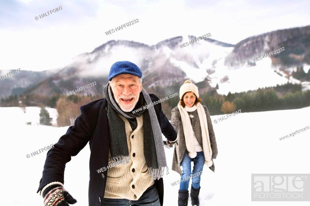 Stock Photo: Portrait of senior man walking hand in hand with his wife in snow-covered landscape.