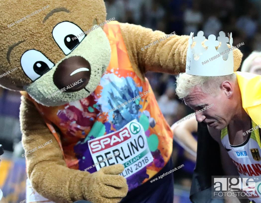 Stock Photo: 08.08.2018, Berlin: Athletics, European Championships in the Olympic Stadium: Decathlon, 1500 m, Men, Arthur Abele from Germany celebrates gold with mascot.