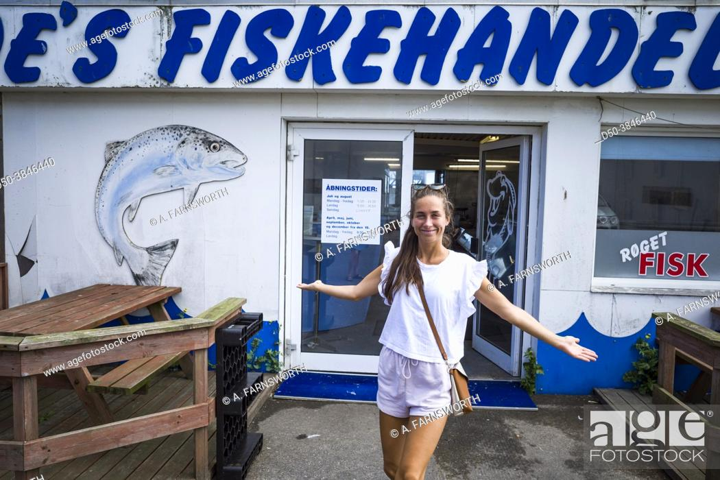 Stock Photo: Hirtshals, Denmark July 8, 2021 A young woman posing in front of a local fish store.