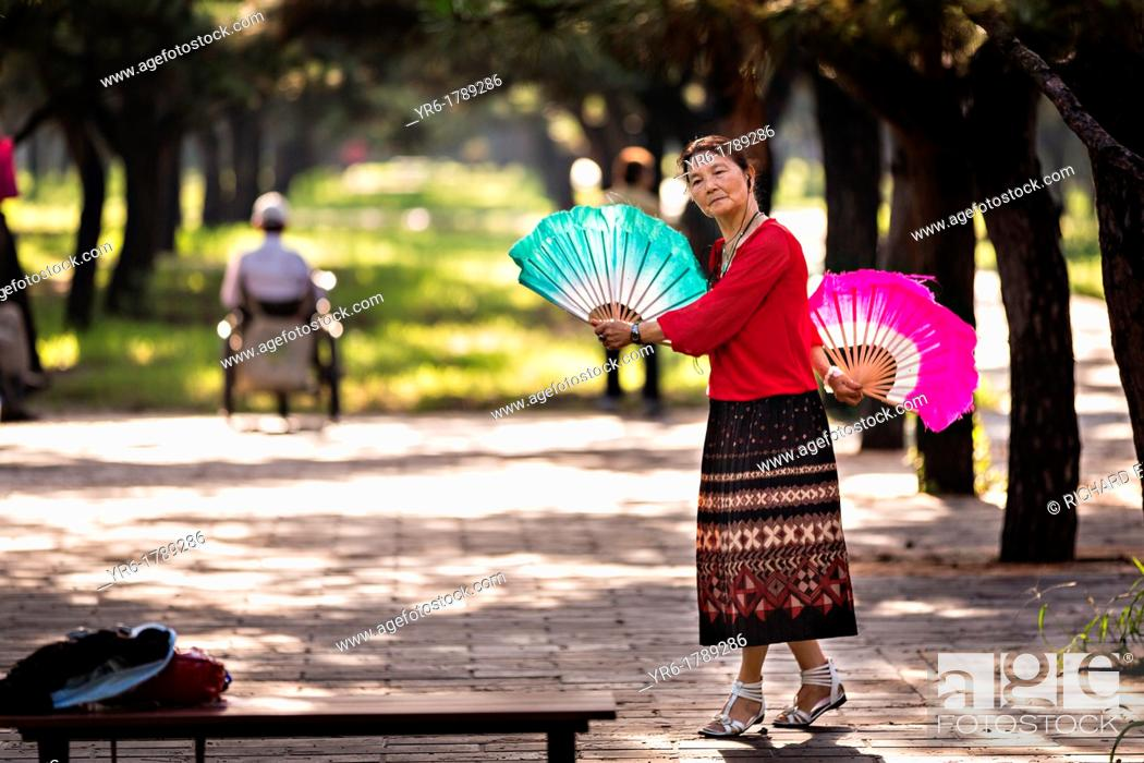 An elderly Chinese woman practices tai chi fan dance martial arts