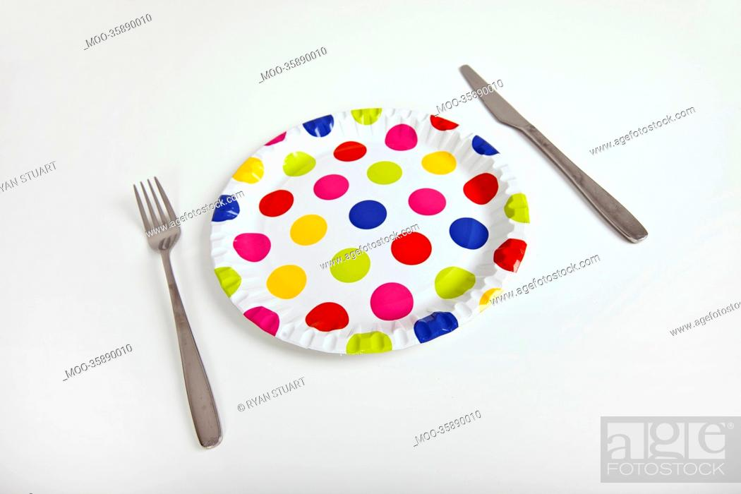 Stock Photo: Multicolored plate with polka dots and cutlery over white background.