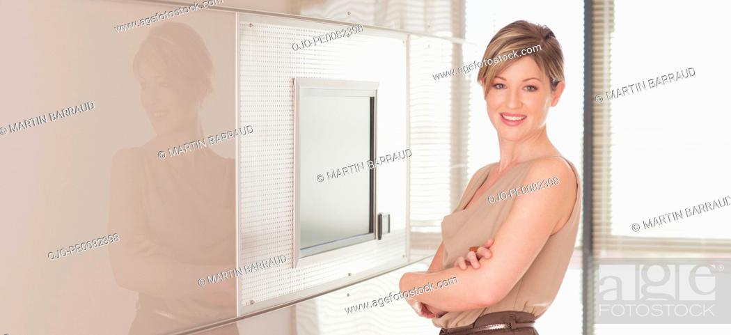 Stock Photo: Portrait of smiling businesswoman with arms crossed.