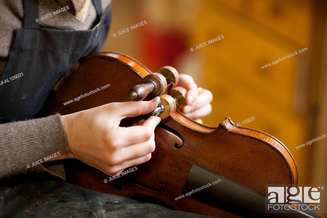 Stock Photo: Violin maker restoring a violin.