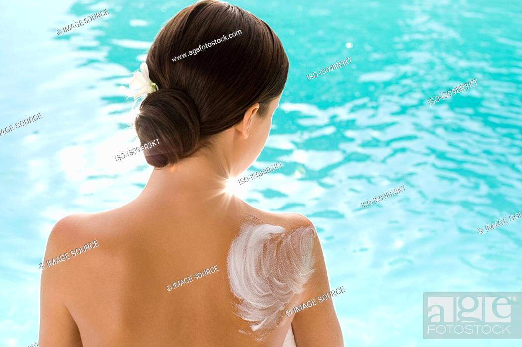 Stock Photo: Rear view of woman sitting by pool with lotion on shoulder.