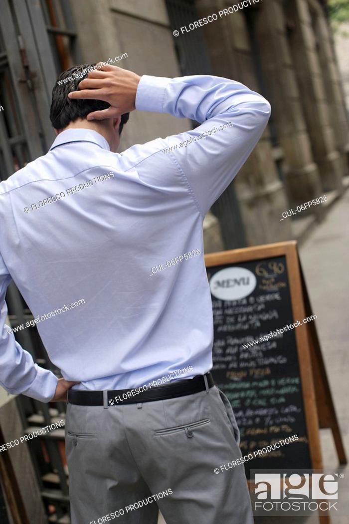 Stock Photo: Business man looking at menu.