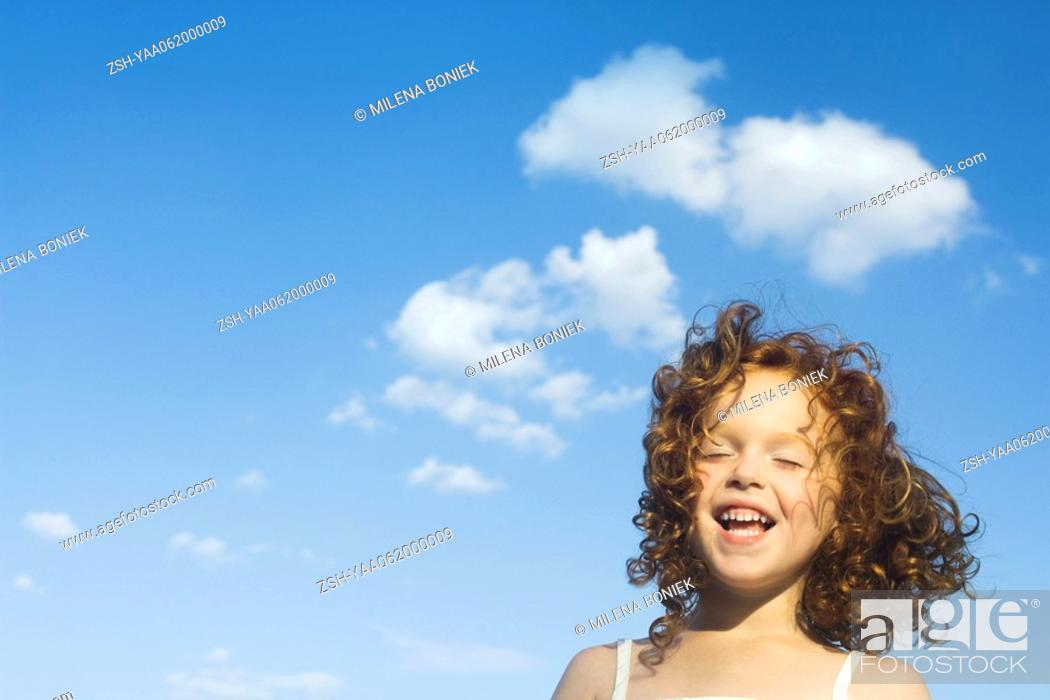 Stock Photo: Little outdoors with tousled hair, eyes closed, smiling.