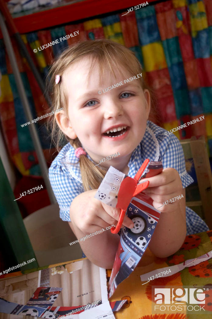 Stock Photo: 4 year old girl at nursery, smiling into camera, cutting.