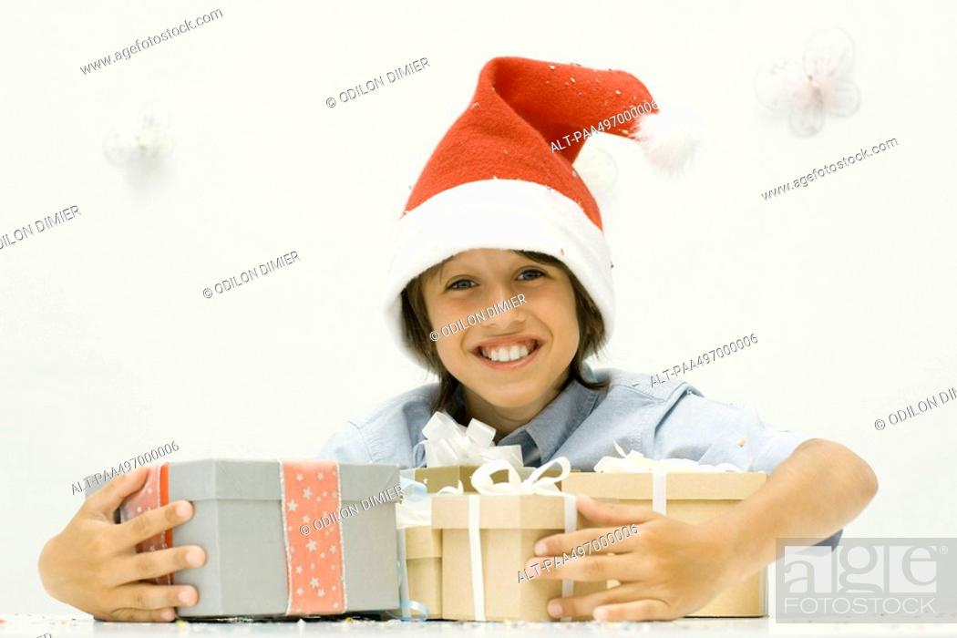 Stock Photo: Boy holding stack of Christmas gifts, wearing Santa hat, smiling at camera.
